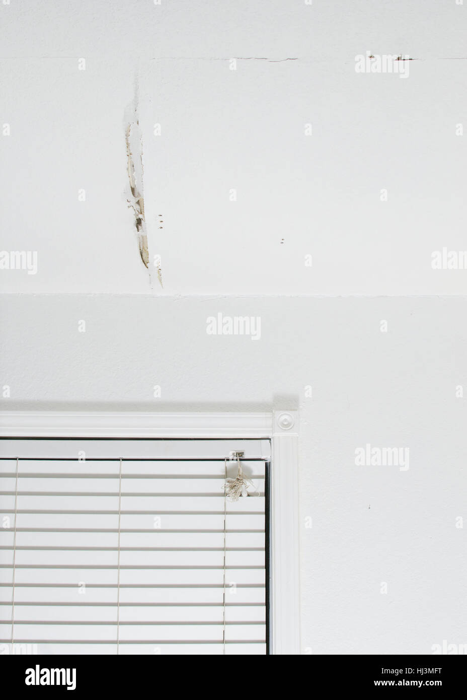 A crack in a white ceiling of  a generic, unidentified old house, resulting from water leak, showing a bulged panel - Stock Image