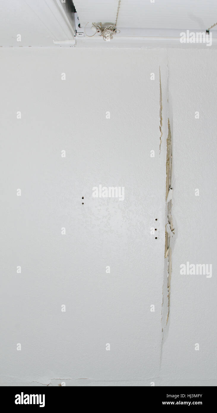 A crack in a white ceiling of  a generic, unidentified old house, viewed from below, resulting from water leak, - Stock Image