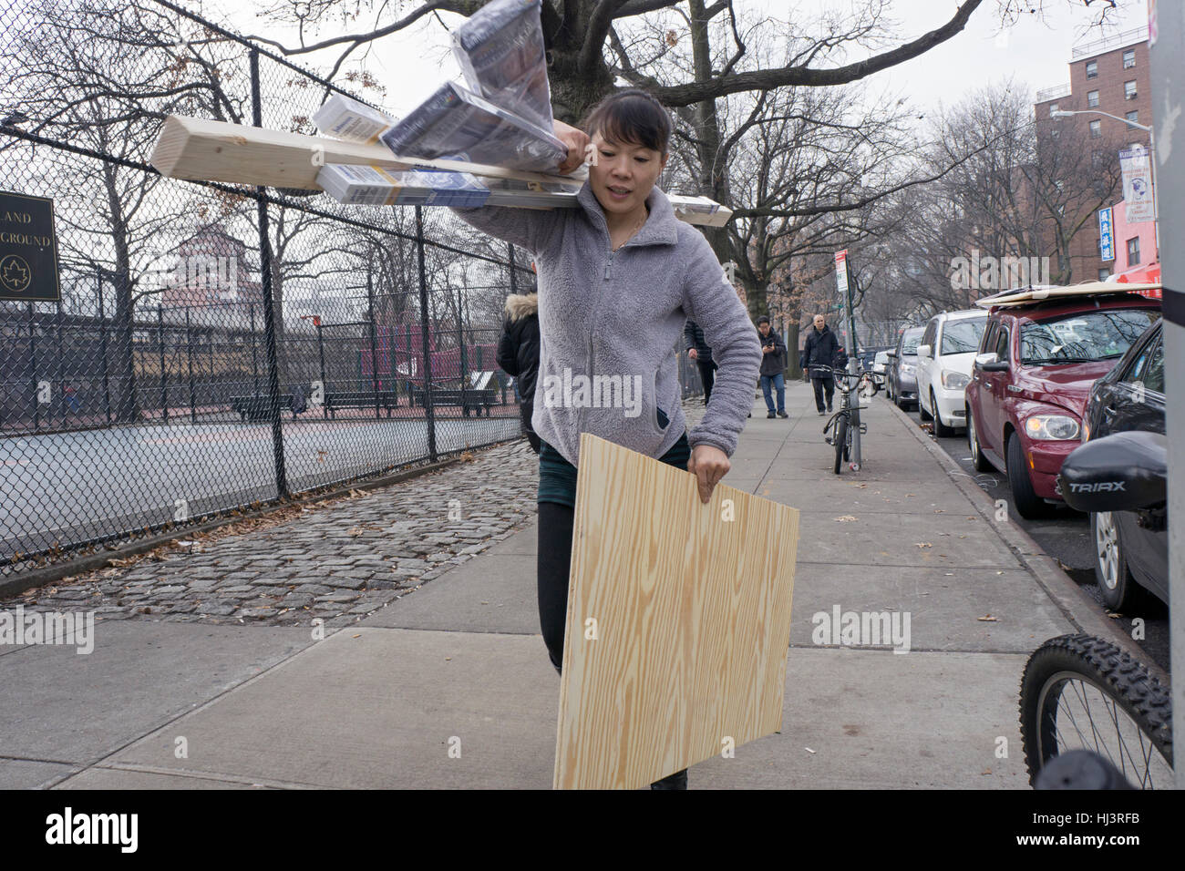 A Chinese American woman carrying wood and lumber to a construction site in Chinatown, downtown Flushing, Queens, New York. Stock Photo