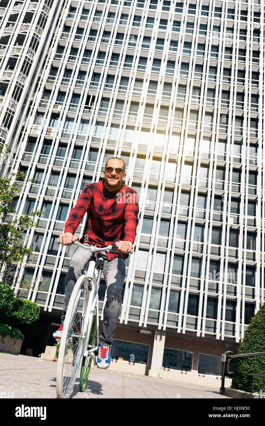 Handsome young man on bike in the city. Bicycle concept - Stock Image