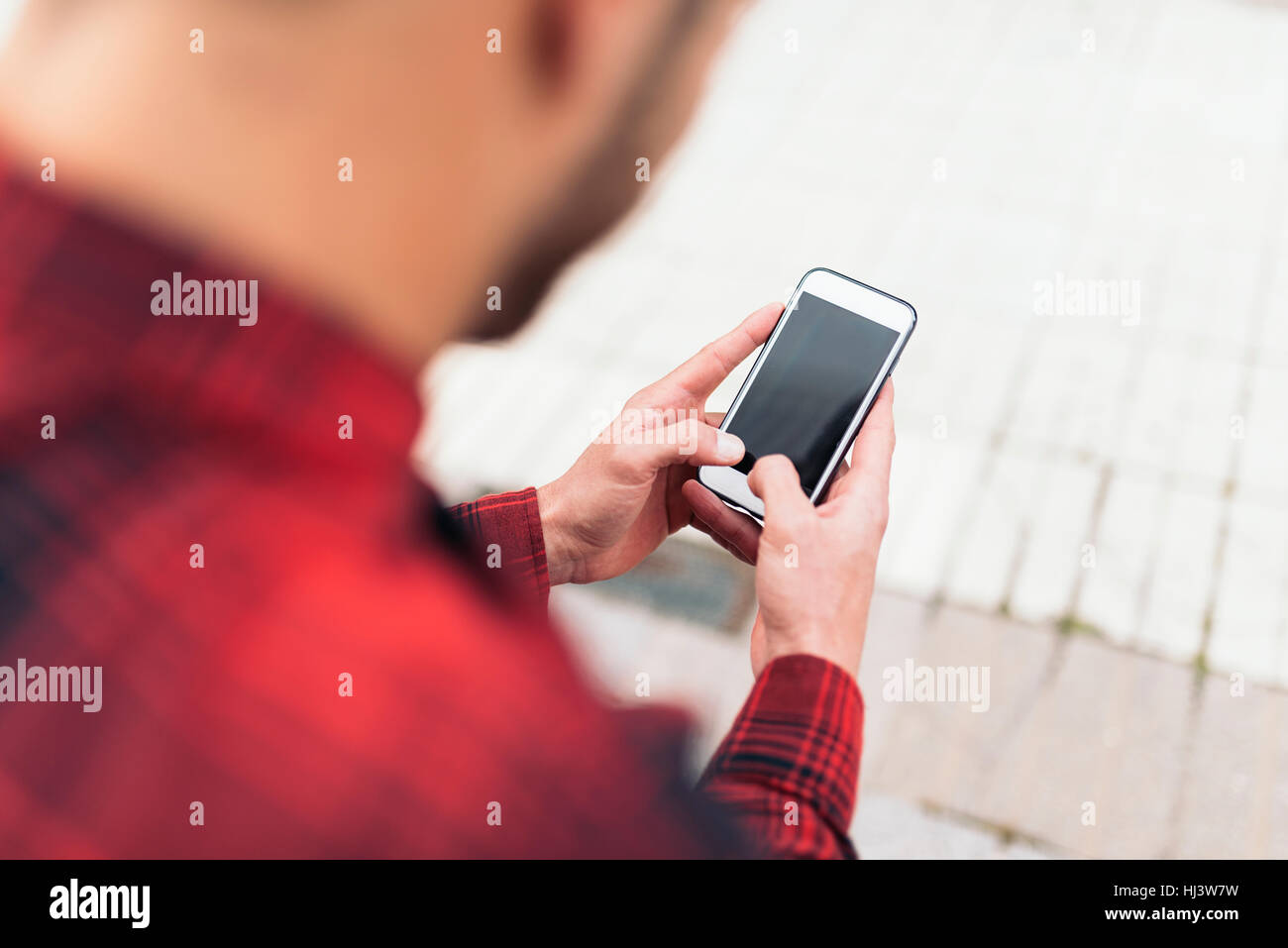 Young man using his mobile in the street. - Stock Image