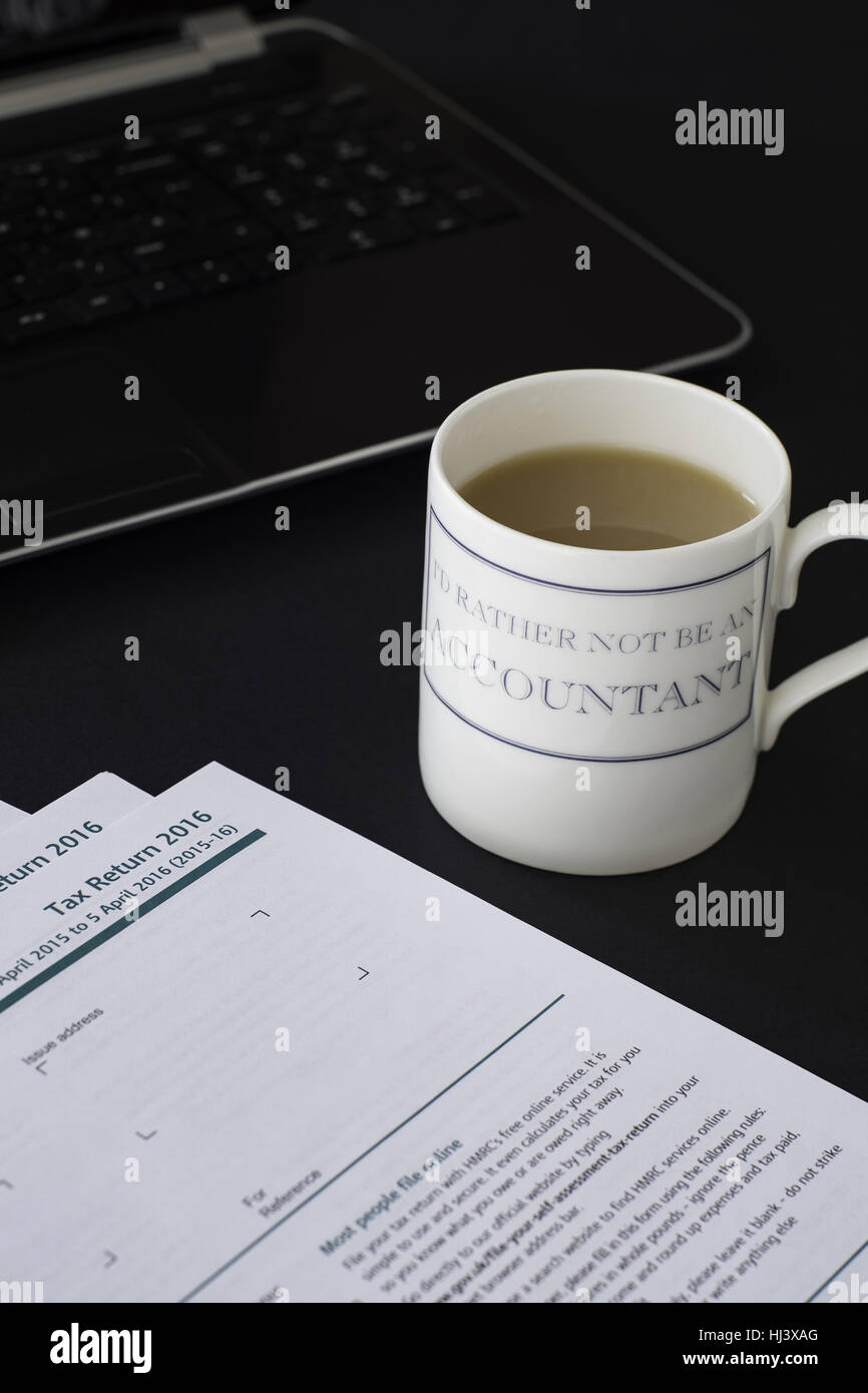 'I'd rather not be an accountant' mug next to blank UK tax returns for accountants stressed by tax return completion. - Stock Image
