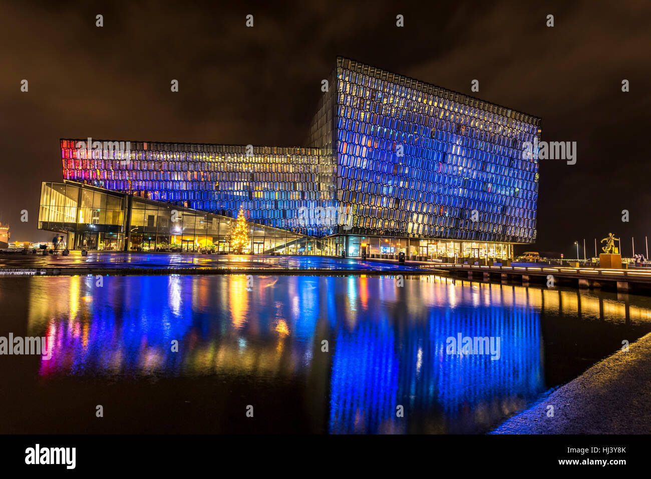 Harpa concert hall in Iceland at night lights up in multiple colors, reflecting on a pool at the front of the building. - Stock Image
