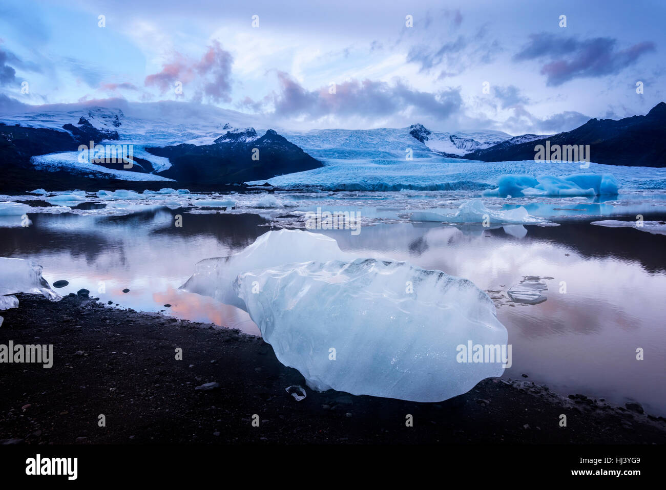 Icebergs along the shore of Jokulsarlon glacial lagoon during a blue overcast day rest motionless while framed by - Stock Image