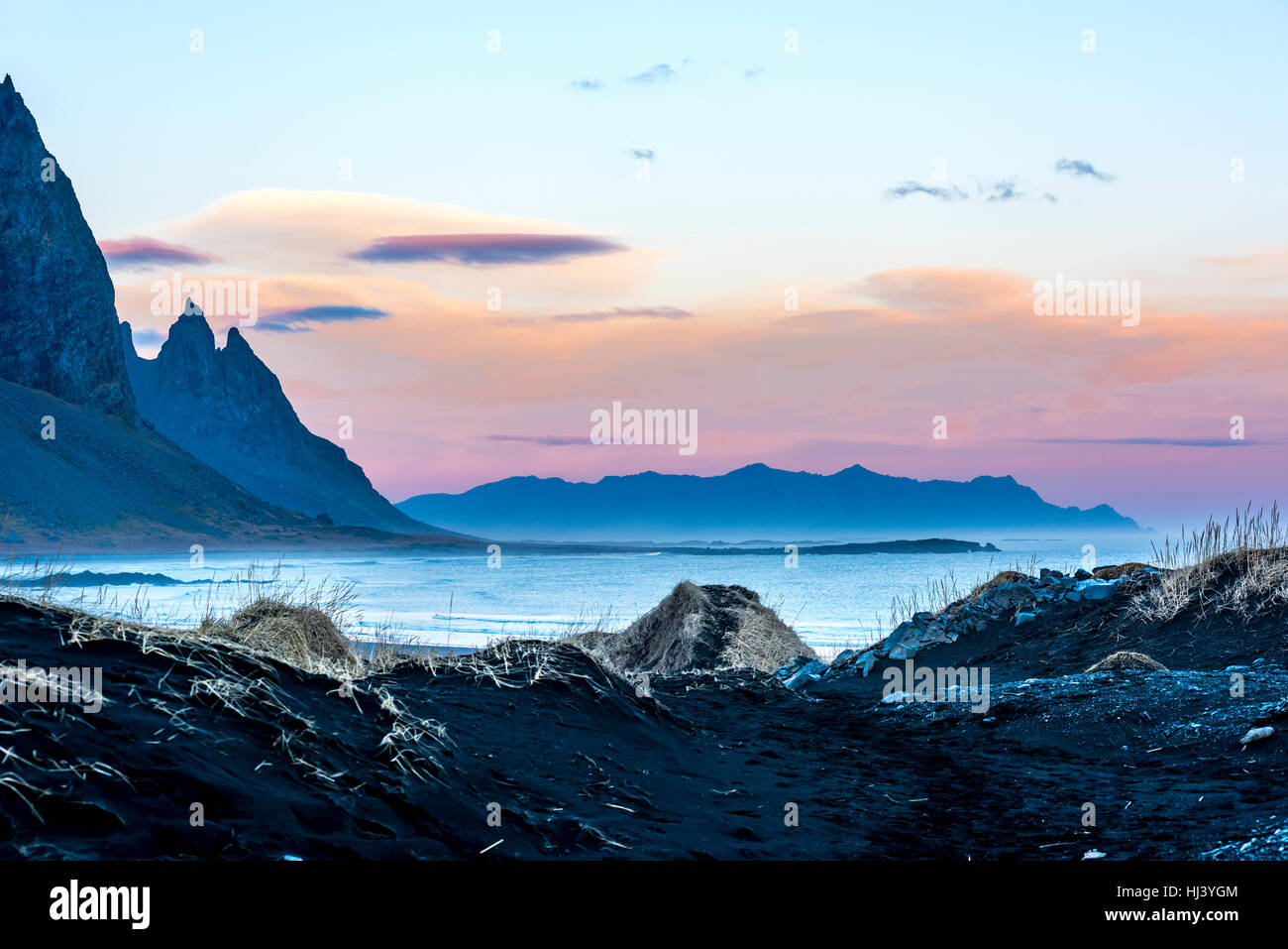 A volcanic sand beach in Iceland framed against jagged mountains and a beautiful pastel sunset as day slips into - Stock Image