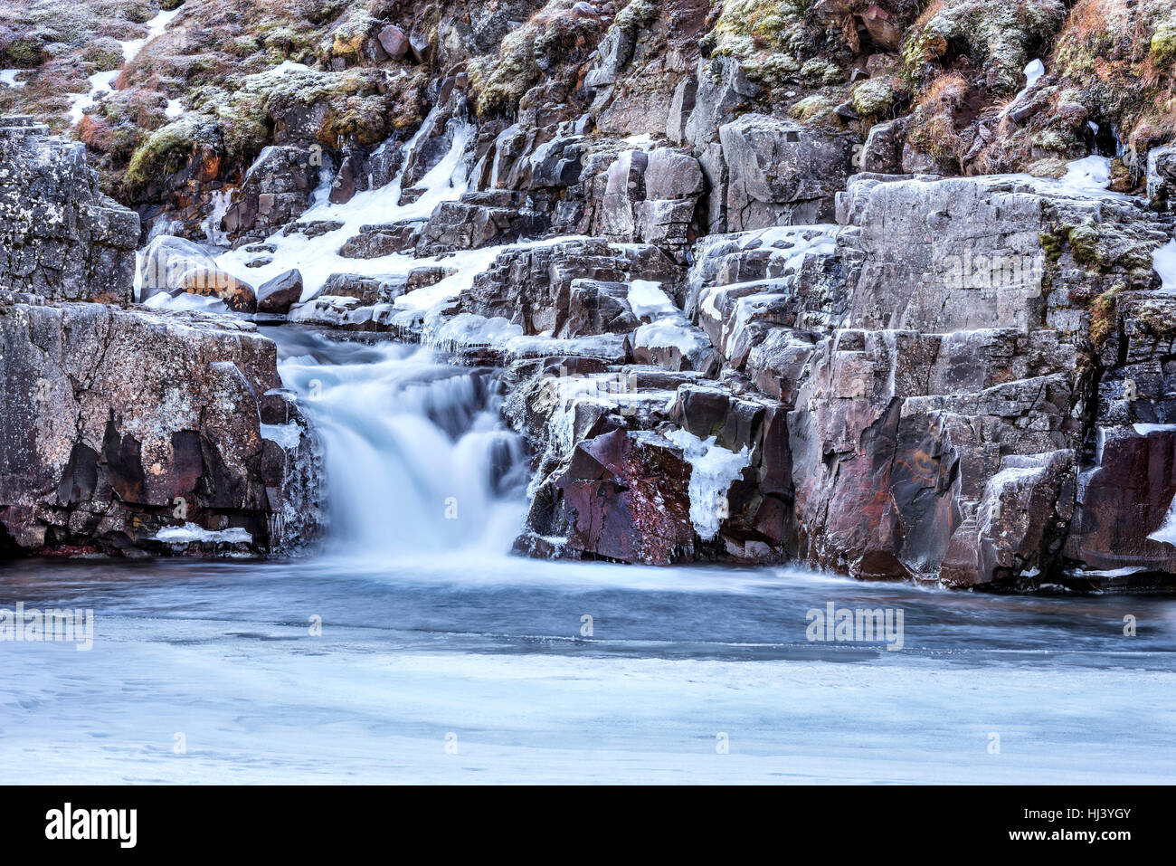 A waterfall surrounded by ice and snow in the highlands of Iceland framed rugged terrain offers scenic landscape - Stock Image