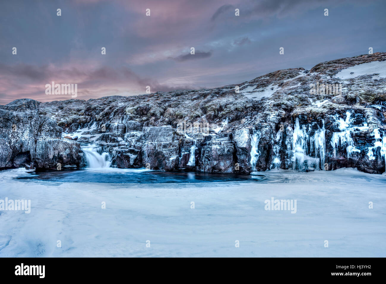 A frozen river in the highlands of Iceland framed by dark pastel skies and rugged terrain offers scenic landscape - Stock Image