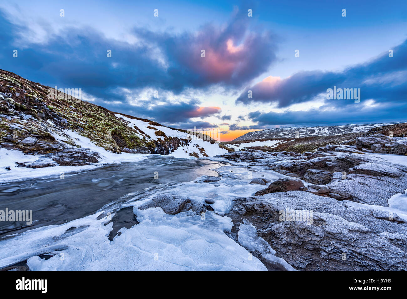 A cold snowy river in the highlands of Iceland framed by pastel skies and rugged terrain offers scenic landscape Stock Photo