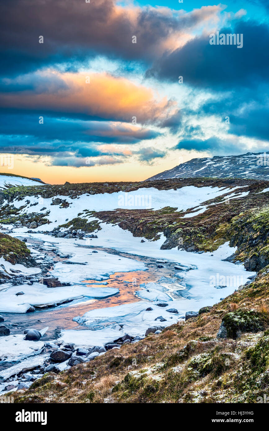 A frozen river in the highlands of Iceland framed by pastel skies and rugged terrain offers scenic landscape epitomizing - Stock Image