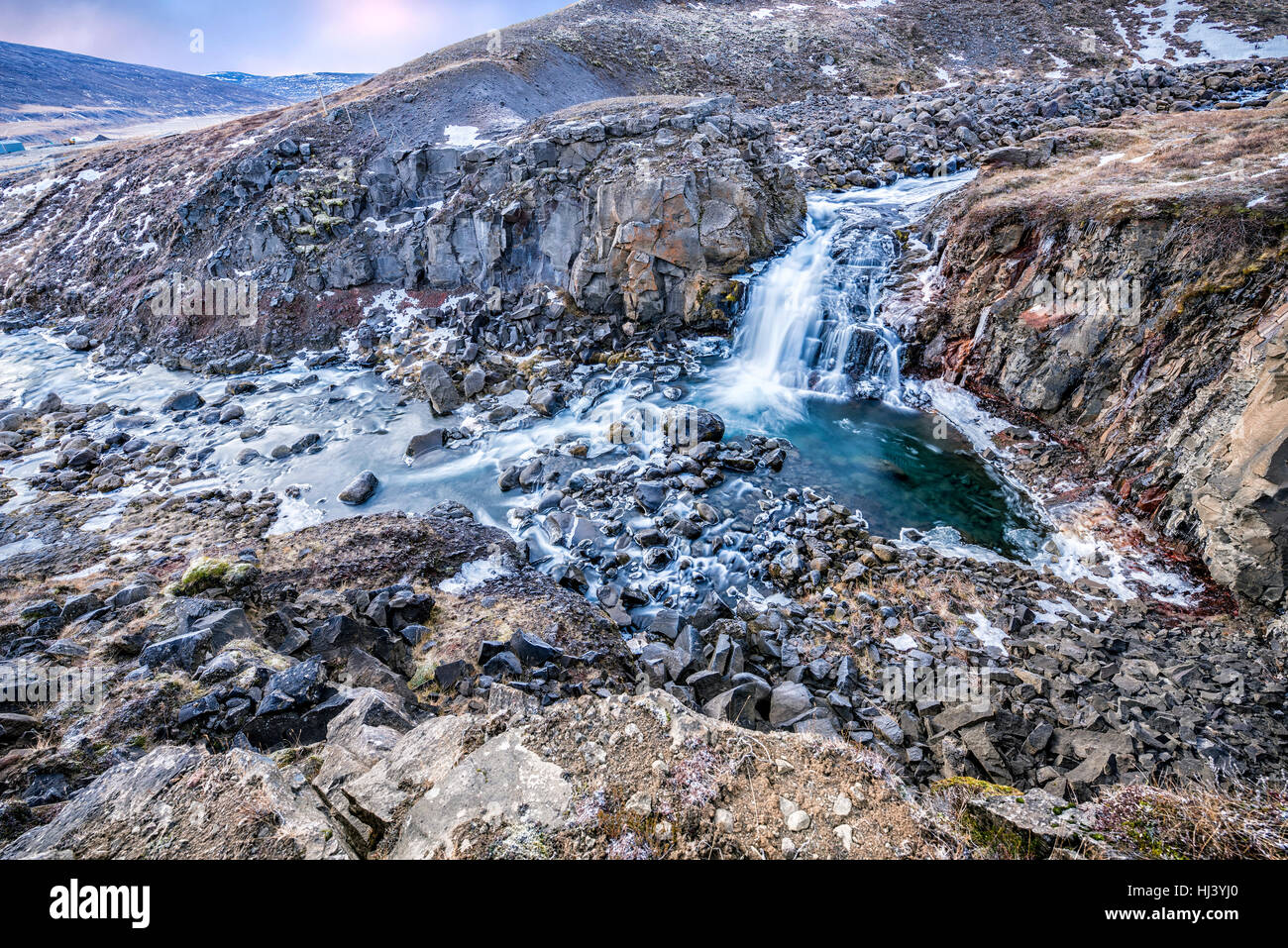 A waterfall in Iceland cascades down the side of a rugged mountain into a natural pool - Stock Image
