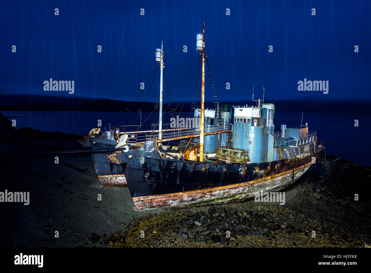 Two abandoned whaling ships rest on a remote beach after Iceland scrapped their whaling program. Ships are light - Stock Image