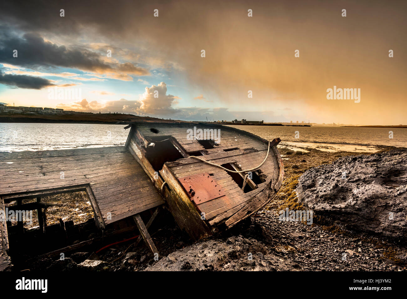 An old abandoned fishing vessel from the early 1900's rests on a remote beach as it rots, exposing the ship's - Stock Image