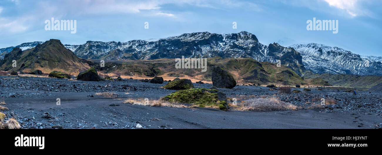 An Iceland mountain range panorama shows the snow-covered mountaintops with dry volcanic landscape and arctic vegetation - Stock Image