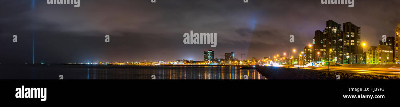 Panorama of Reykjavik Iceland at night shows the bay with bright spotlights and city architecture lining the water. - Stock Image