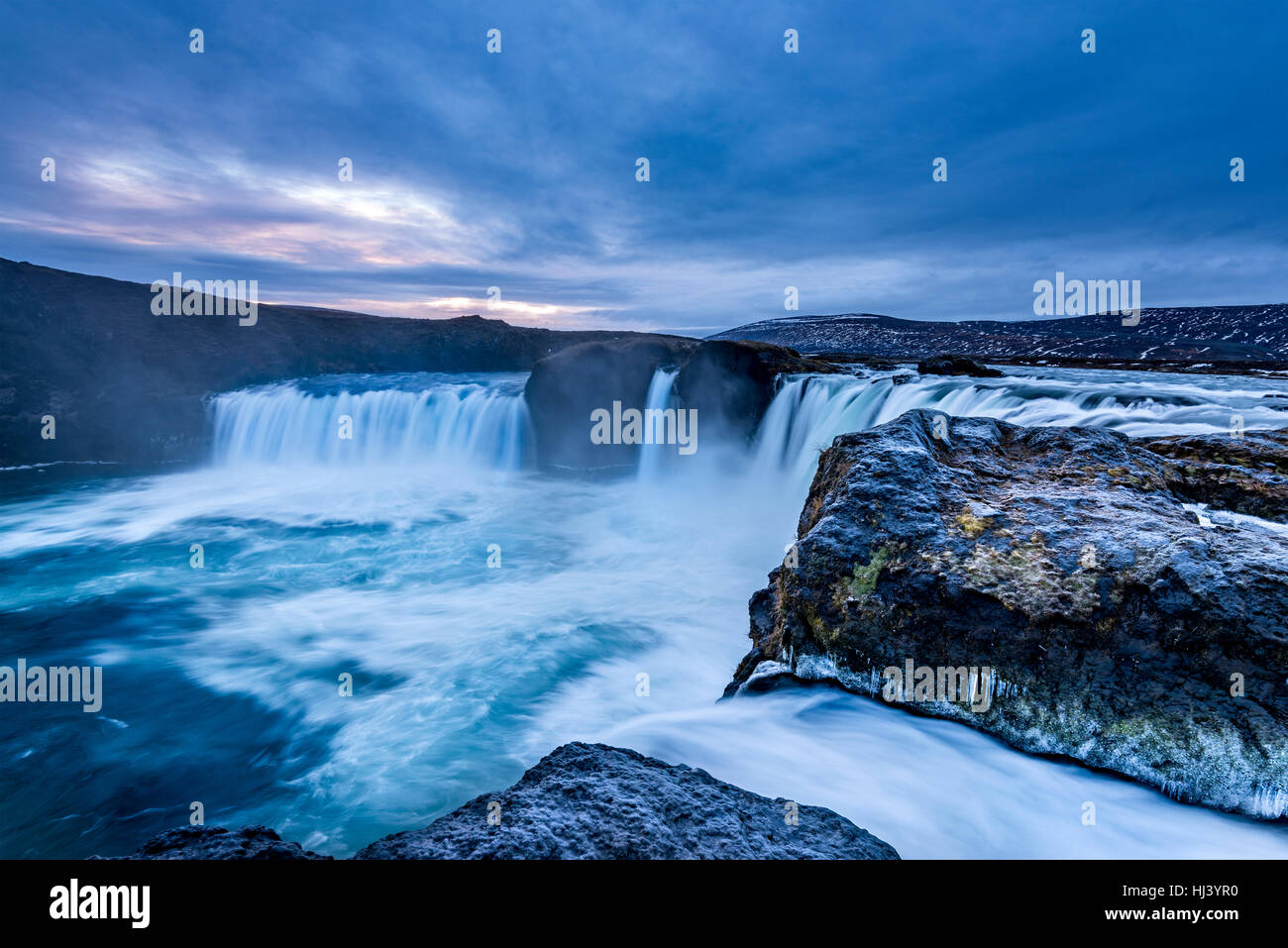 Godafoss Falls during Sunrise shows the water pouring over the edge and kicking up a misty cloud over the water - Stock Image