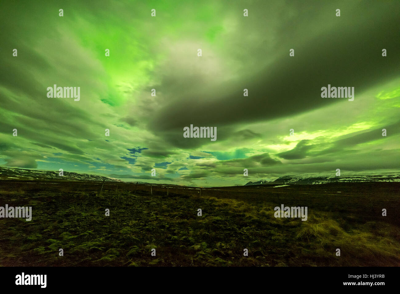 Aurora Borealis glows over a frozen lake surrounded by low cloud cover and stars - Stock Image