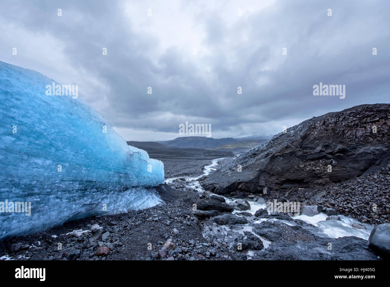 The side of a melting glacier in a rugged Iceland wilderness forms a small stream running down the mountainside - Stock Image