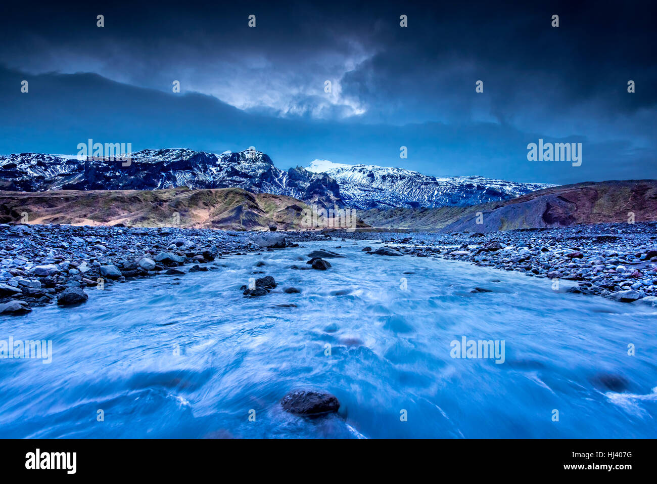 A river formed by melting glaciers flows through a mountain range in northern Iceland during a dark, rainy day. - Stock Image