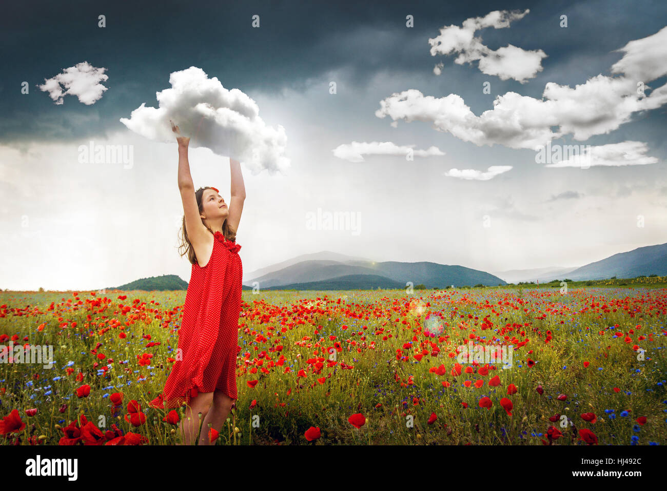 Surreal lifestyle image of young girl in field off poppies catching clouds. - Stock Image