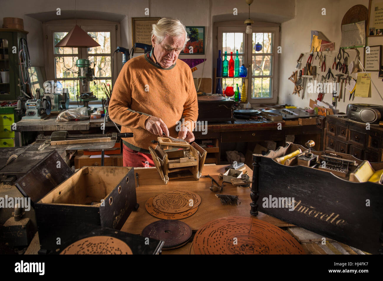Barrel organ builder, workshop, man checks spring wires of sound post on body, empty case on the left, perforated - Stock Image