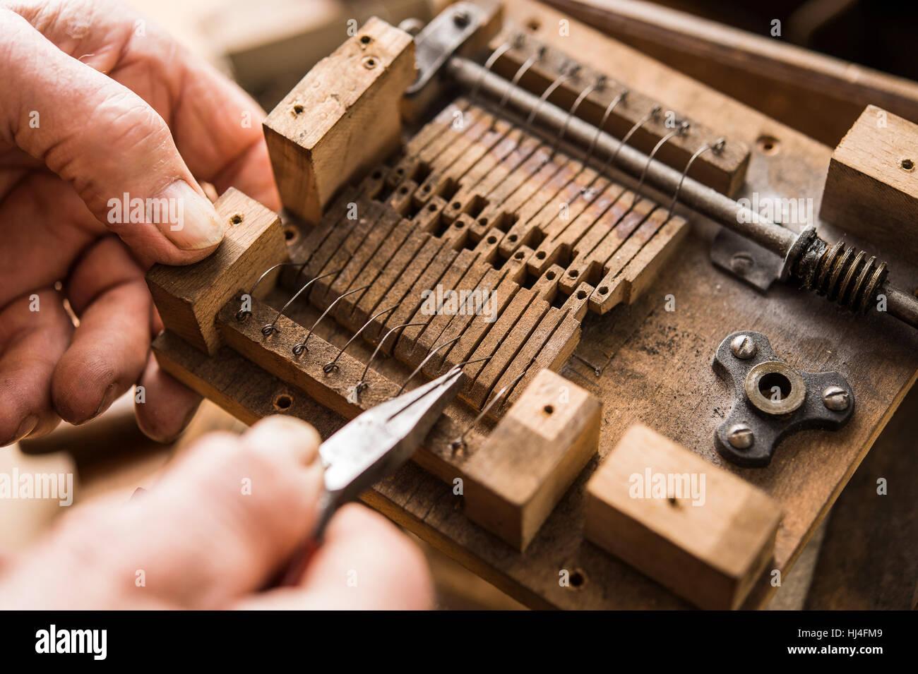 Barrel organ builder, hand bends spring wires made of V2A steel into wooden valves, Grassau, Upper Bavaria, Bavaria, - Stock Image