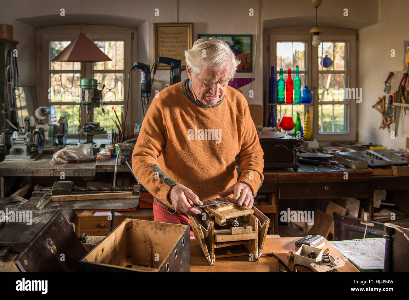 Barrel organ builder, workshop, man puts sound post between bellows, Grassau, Upper Bavaria, Bavaria, Germany - Stock Image