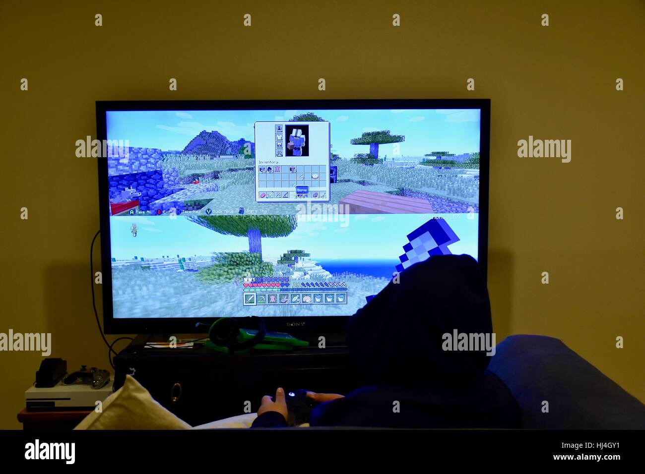 A young teen playing Minecraft on the Microsoft Xbox One S - Stock Image