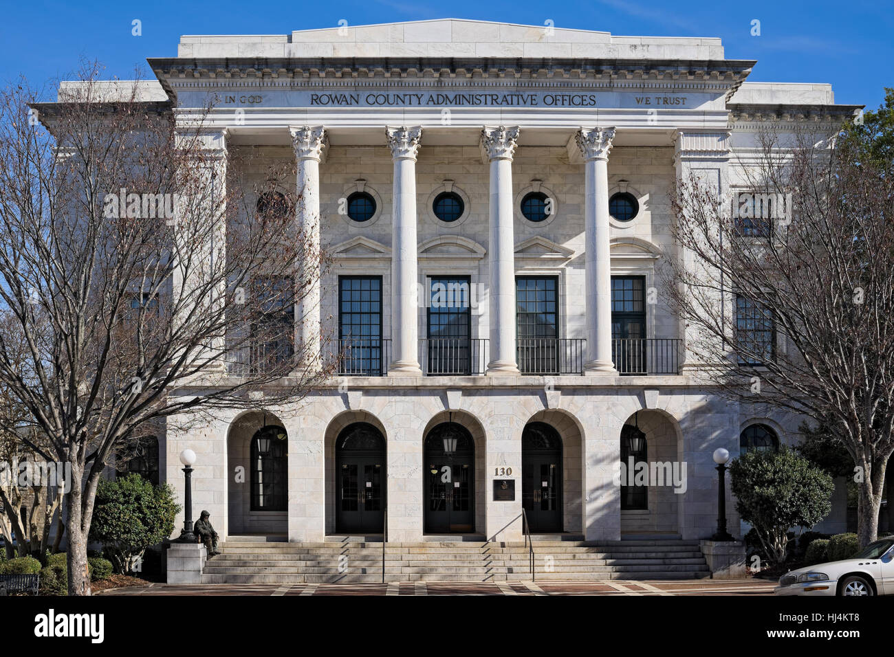 Do you notice or not see? Rown County Administrative Offices building, A man who appears to be homeless sits at - Stock Image