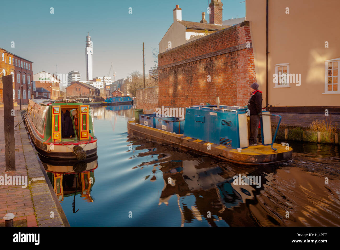 Birmingham Canal Network main line canal, Birmingham city centre with a narrowboat in the middle forground, UK Stock Photo