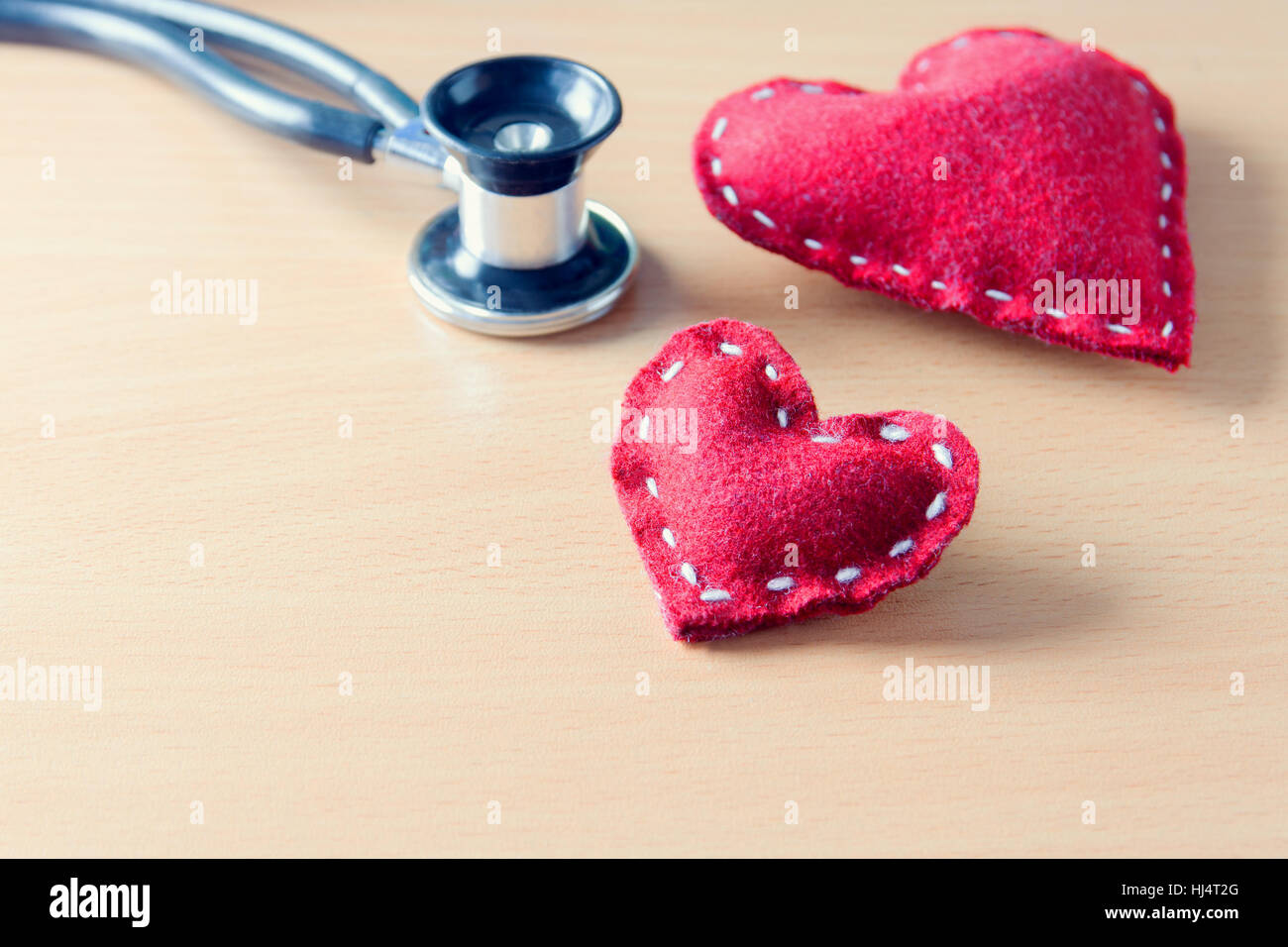 Fabric red heart and stethoscope on wooden table - state on mind, mood or health condition concept, tint image Stock Photo