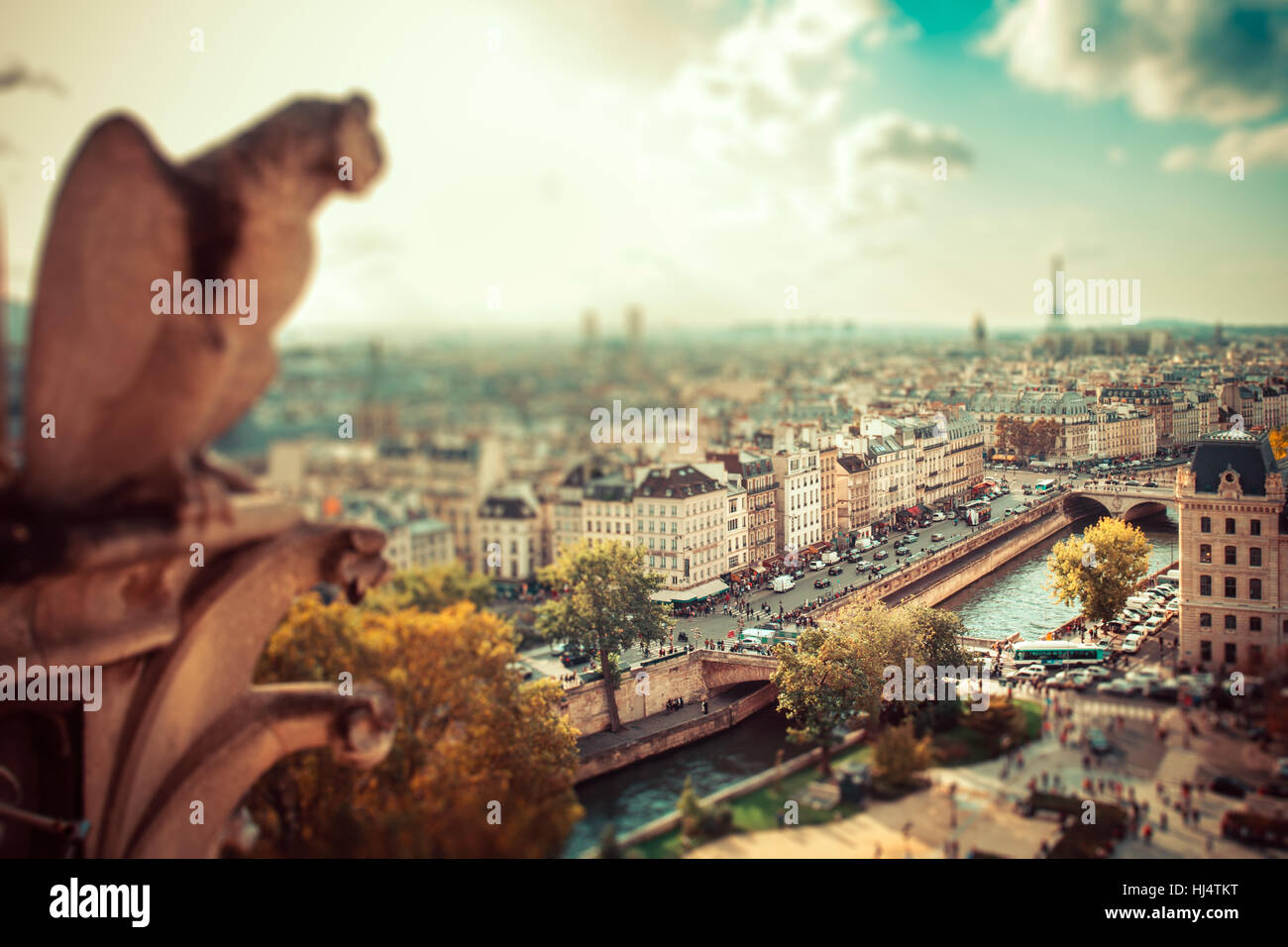 Tilt-shift miniature effect of panoramic view across Paris with gargoyle in foreground - Stock Image