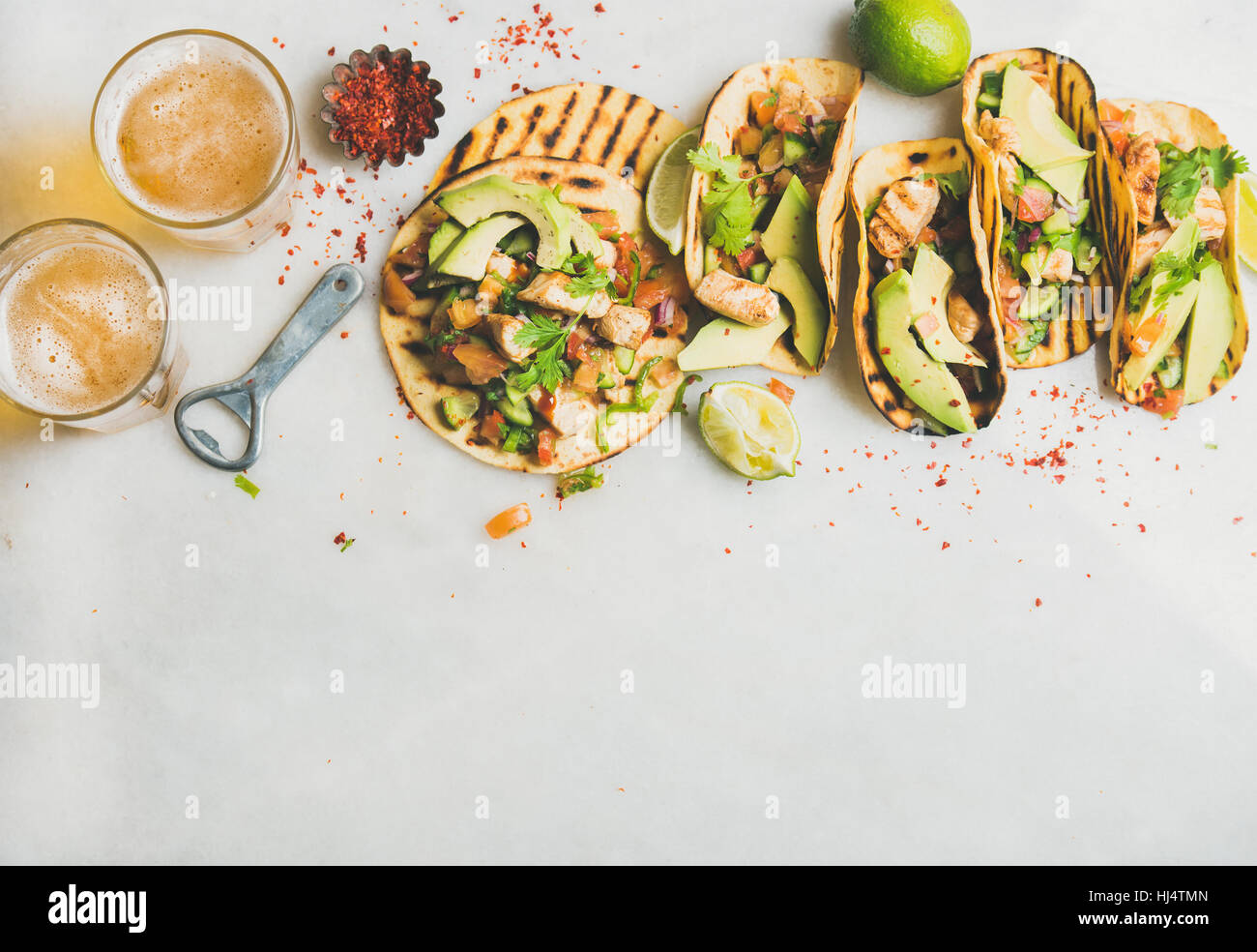 Healthy corn tortillas with grilled chicken, avocado, lime, beer - Stock Image