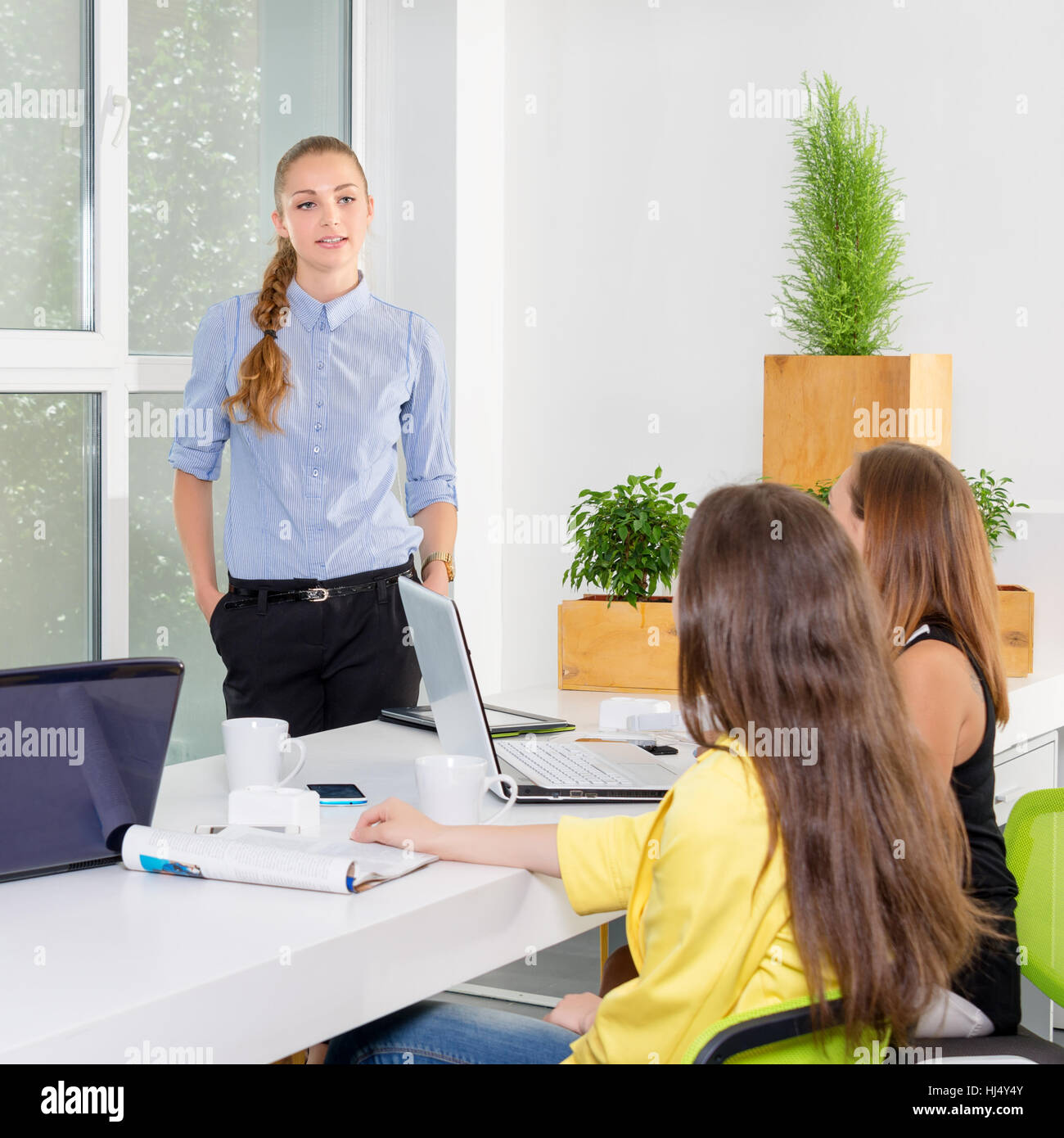 Pretty young business woman giving a presentation in conference or meeting setting. People and teamwork concept - Stock Image
