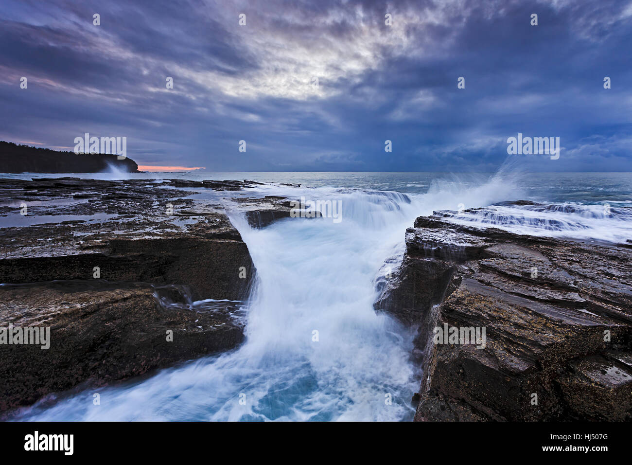 Rugged coastline of Australia Sydney northern beaches at stormy sunrise when strong waves hit crack in coast sandstone - Stock Image