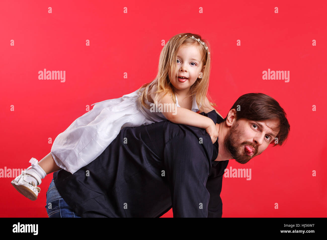 Father and daughter piggyback. They show tongues. Emotional games with your child. Family fun. The joy of communication. - Stock Image