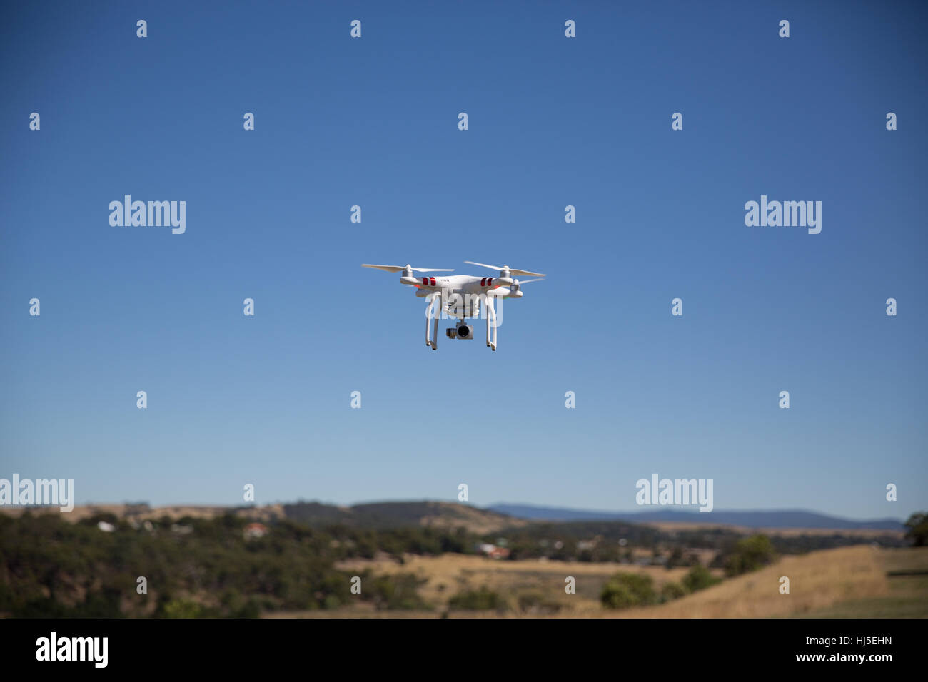 Unmanned Aerial Vehicle (UAV) or Drone, safely flying in a field. - Stock Image