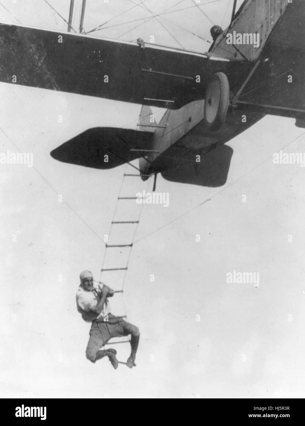 'Fearless Freddie', a Hollywood stunt man, clinging to a rope ladder slung from a plane flown by A.M. Maltrup, - Stock Image