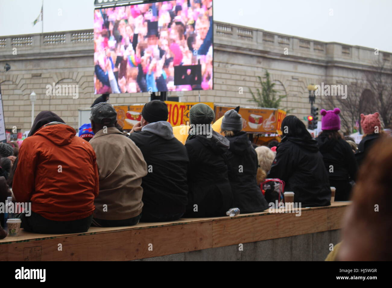 District of Columbia, USA. 21 Jan, 2017. Eight protesters sit along a wall watching a livestream of speakers at - Stock Image