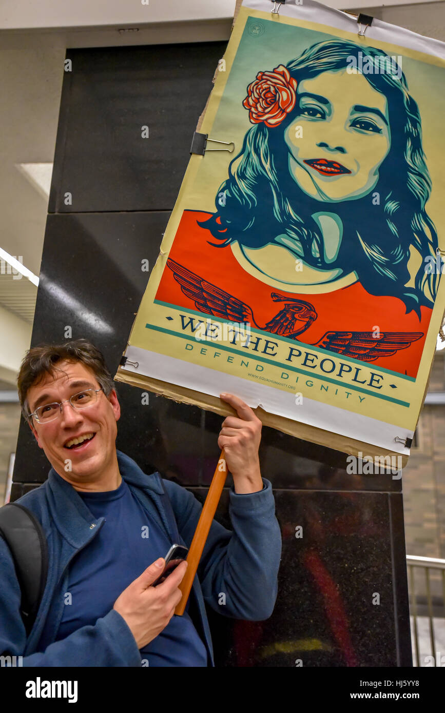 San Francisco, California, USA. 21st January, 2017. Man holds sign 'We the people' with image by artist - Stock Image