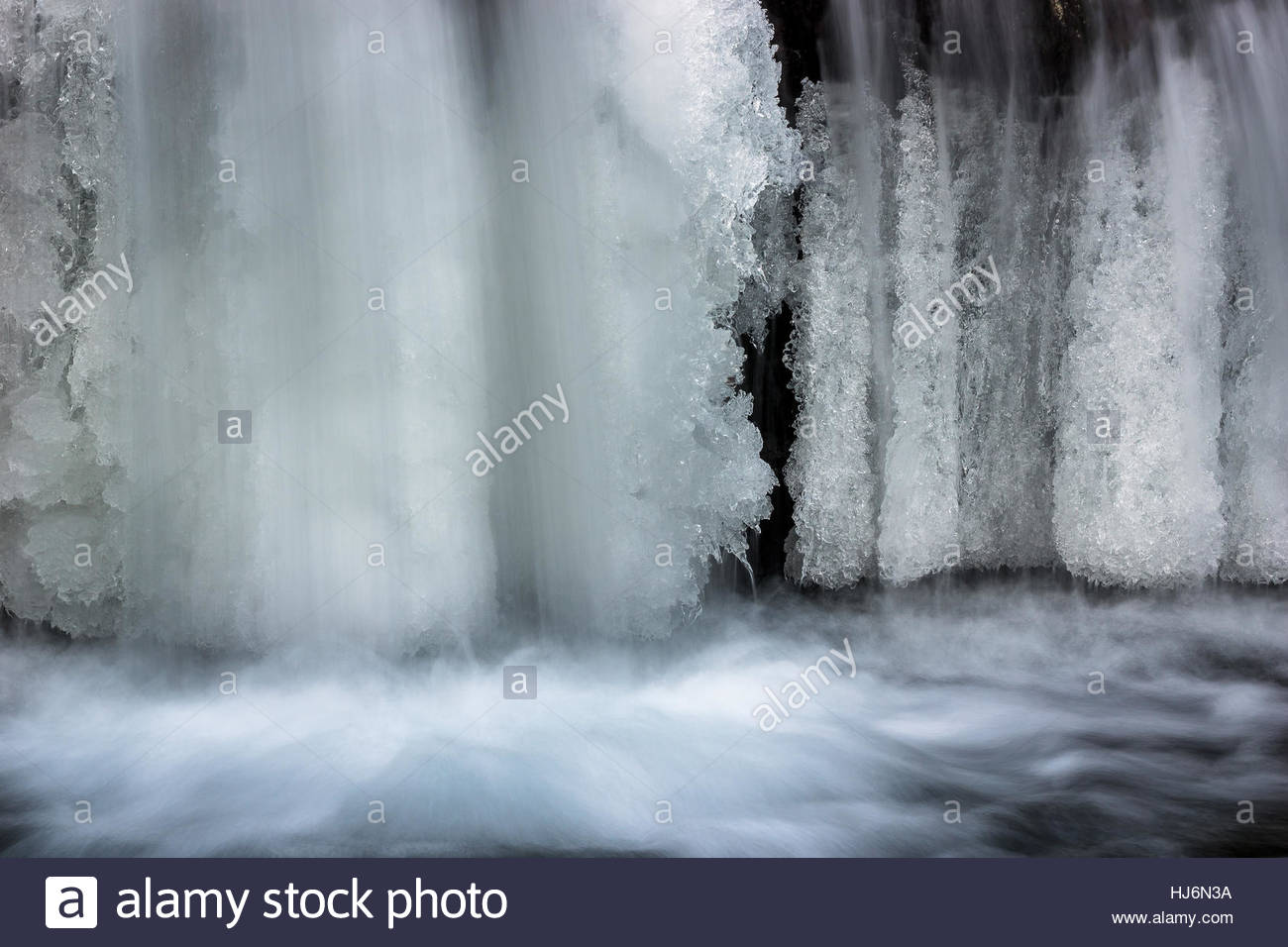 cold winter : ice frozen river banks and beautiful icicles Stock Photo
