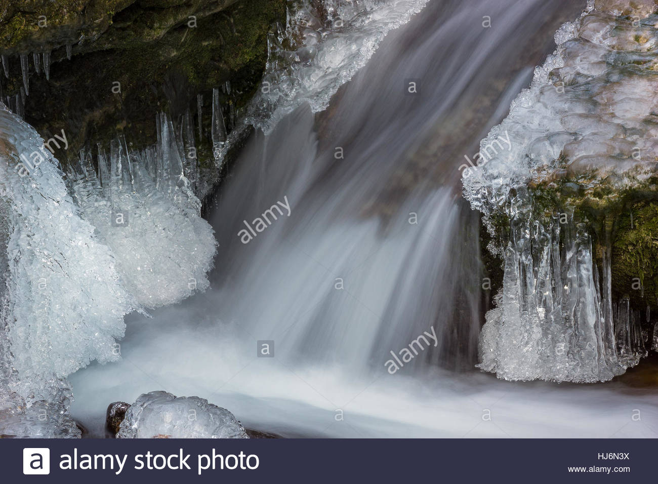 cold winter : ice frozen river banks and beautiful icicles - Stock Image