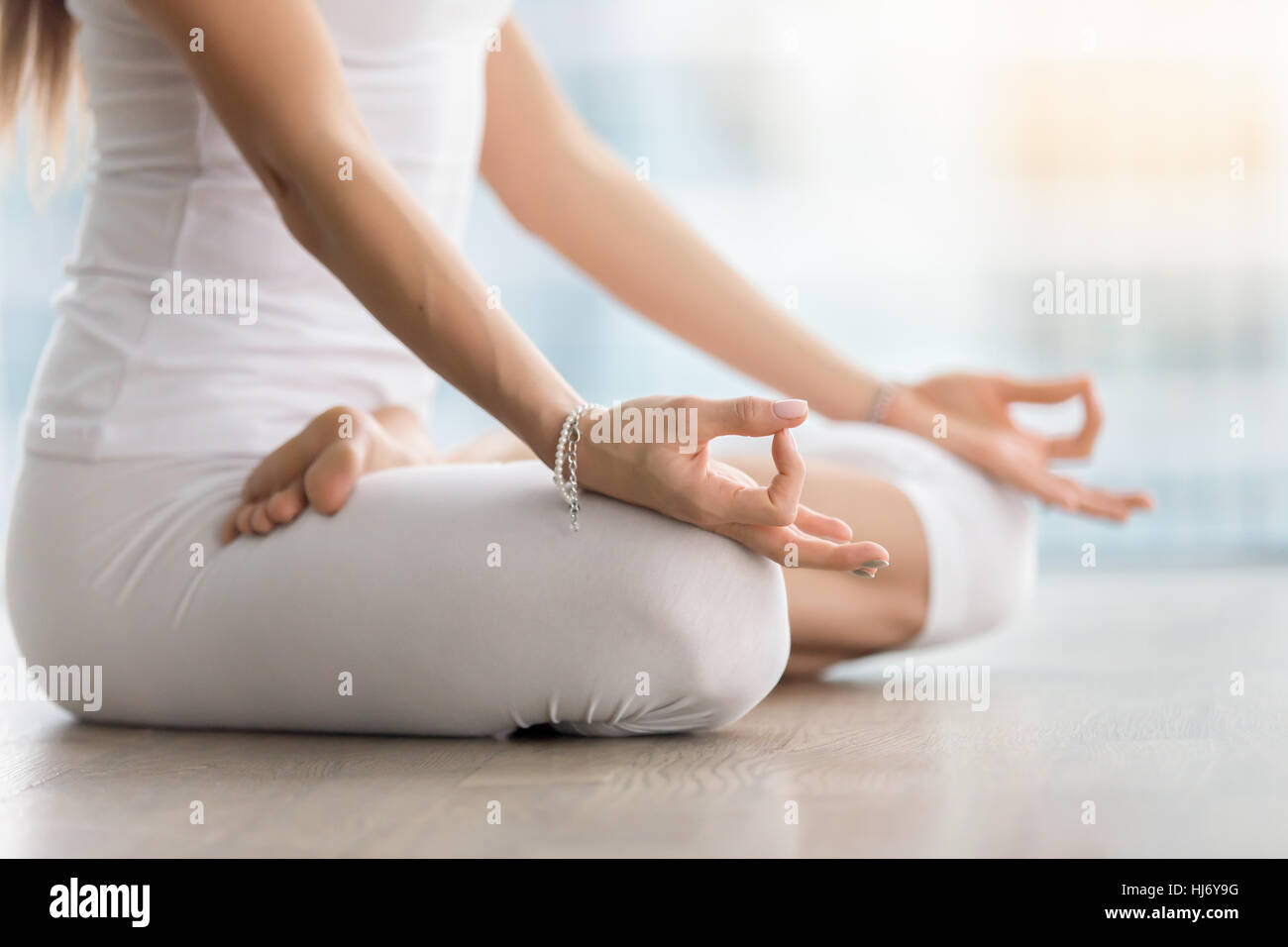 Woman in Padmasana pose with mudra against floor window, closeup - Stock Image