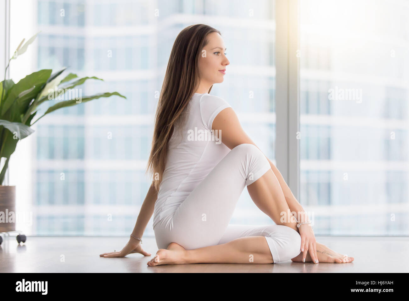 Young attractive woman in Ardha Matsyendrasana pose against floo - Stock Image