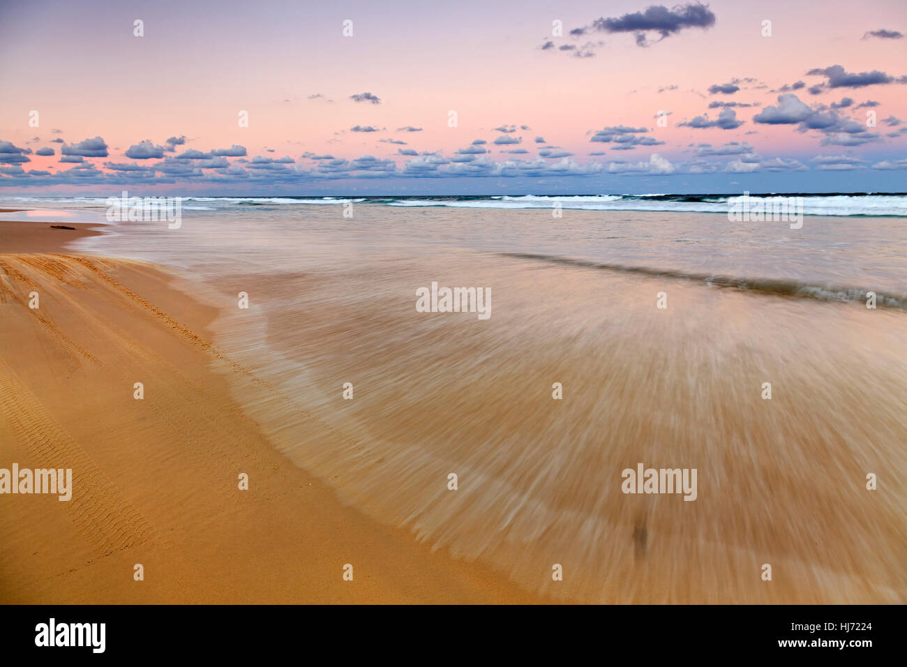 Fraser Island 75 miles beach at sunset long exposure blurred waves and tide over flat sandy shore in Australia, - Stock Image