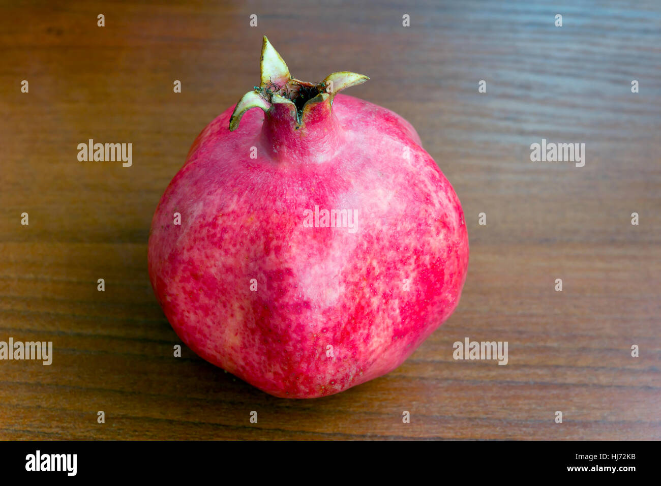Photo of one pomegranate on brown wooden background - Stock Image
