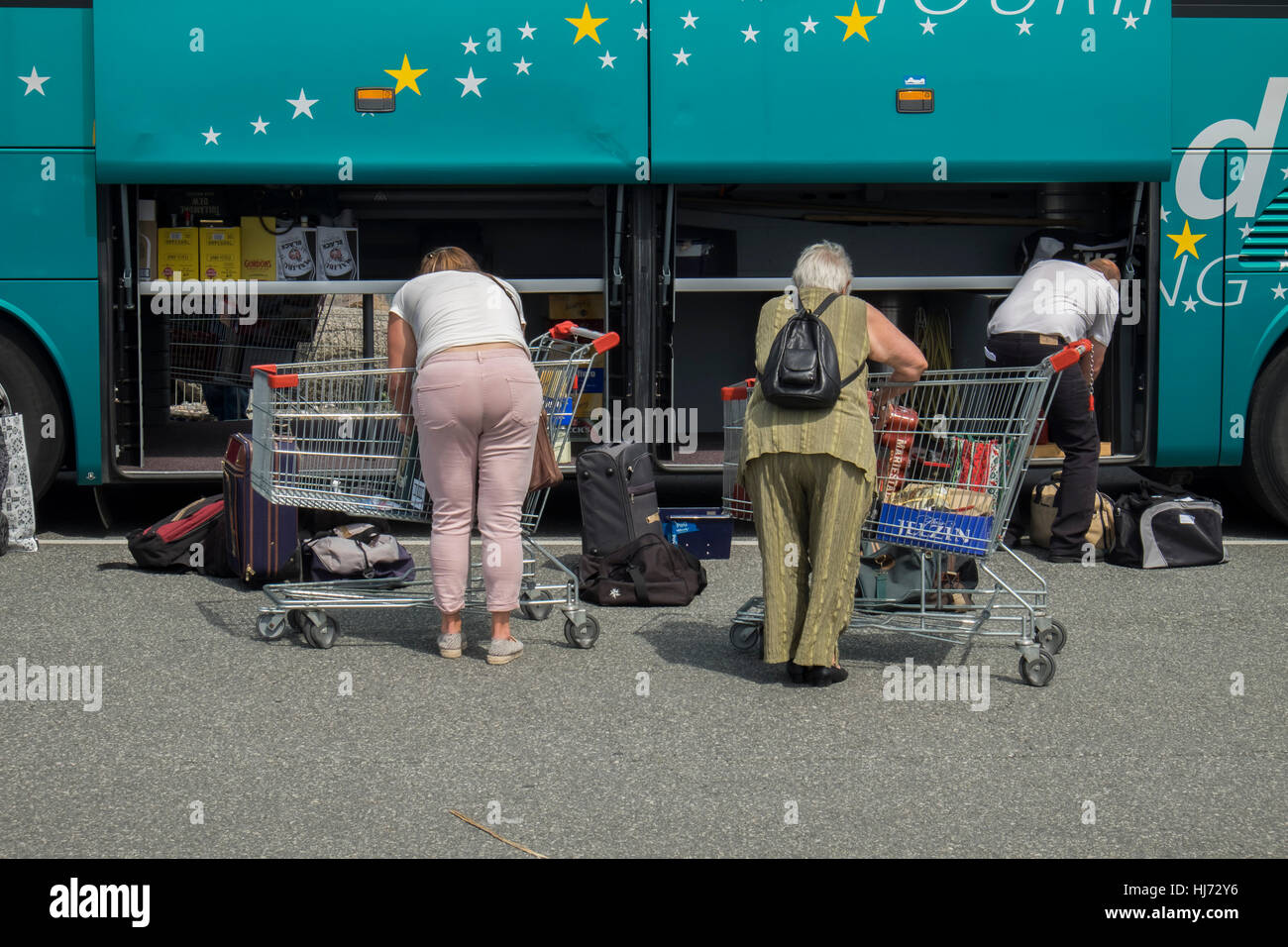 People have shopped at the Border Shop in Germany and unloads now the bus for the journey home. - Stock Image