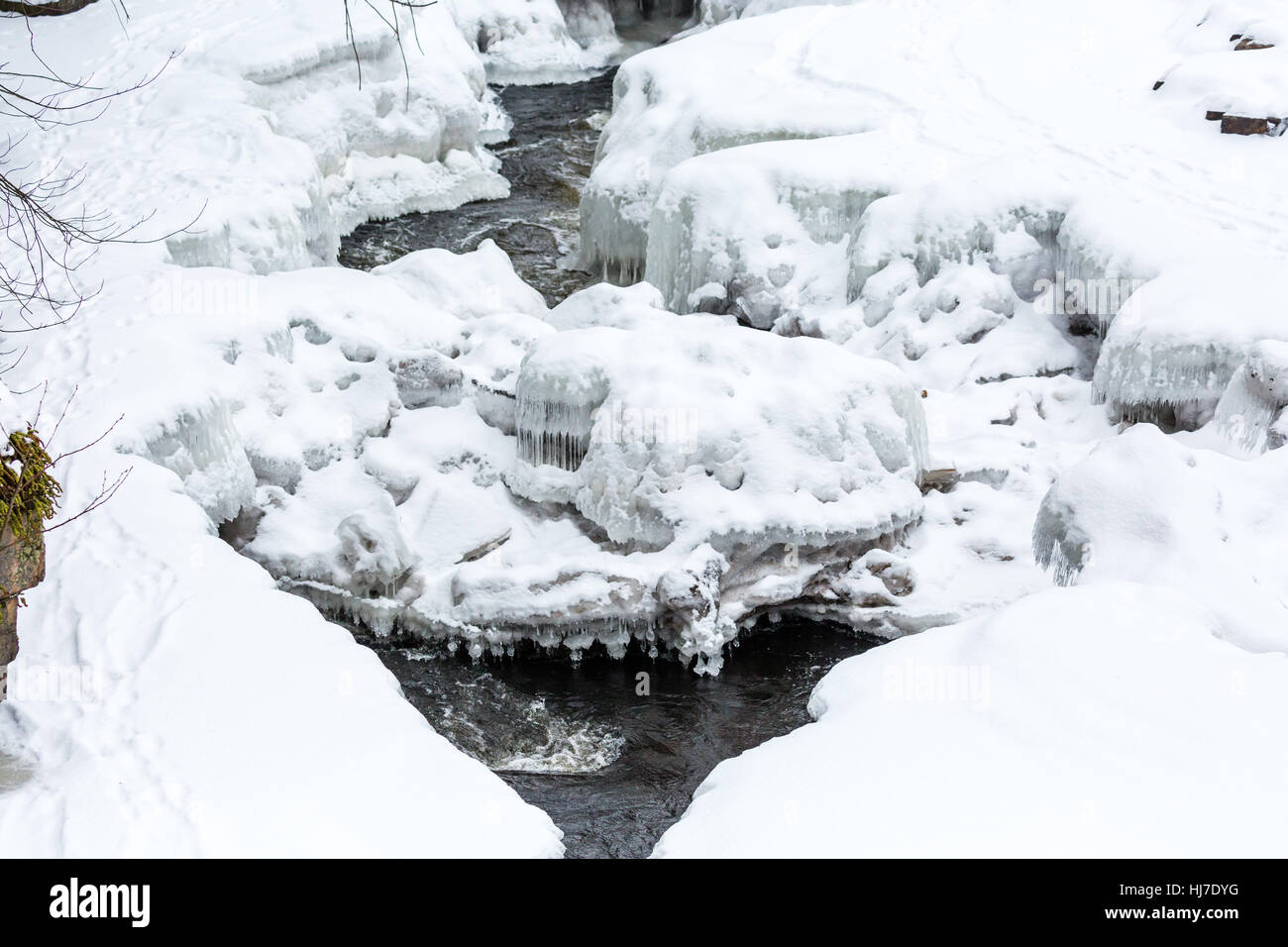 River encased in snow and ice with animal tracks. - Stock Image