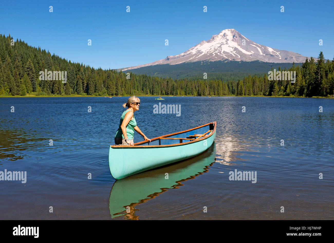 A middle-aged woman with a canoe on Trillium Lake near Mount Hood, in the Mount Hood National Forest, Oregon, in - Stock Image