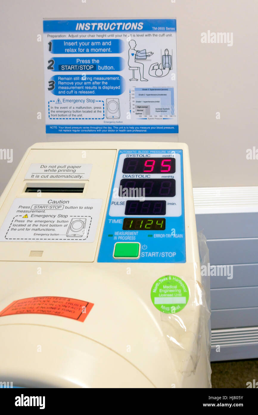 Self service blood pressure testing machine in an NHS General Practitioner's surgery waiting room test in progress - Stock Image
