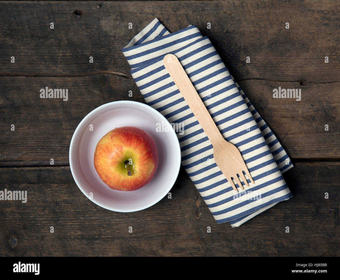Apple in a Bowl with fork and napkin on a rustic wooden table - Stock Image